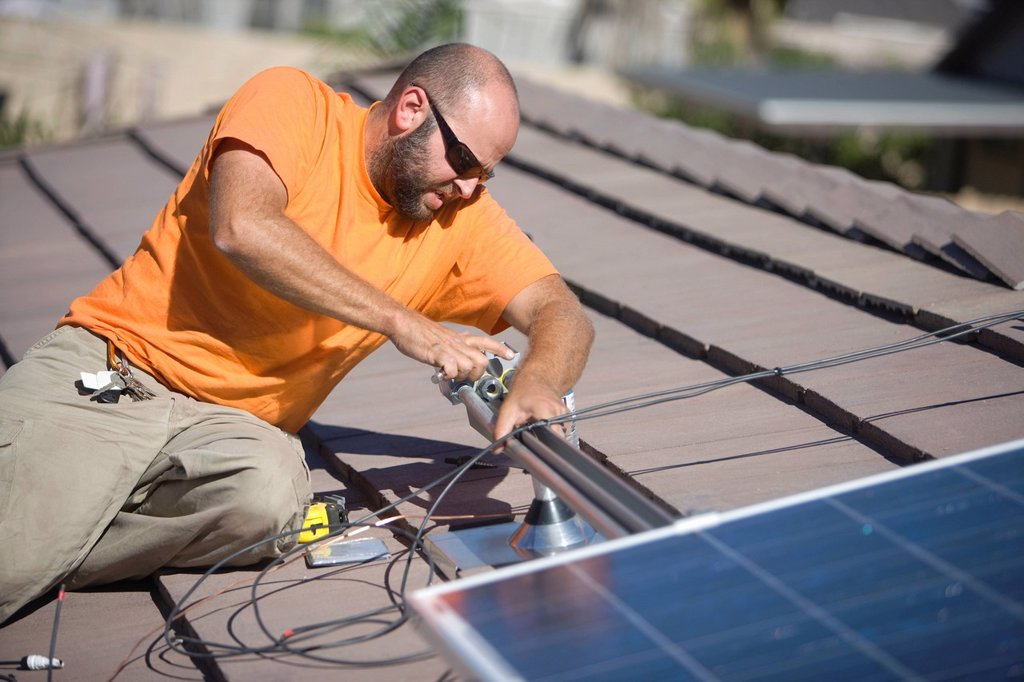 One man working on solar panelling on a roof top : Stock Photo