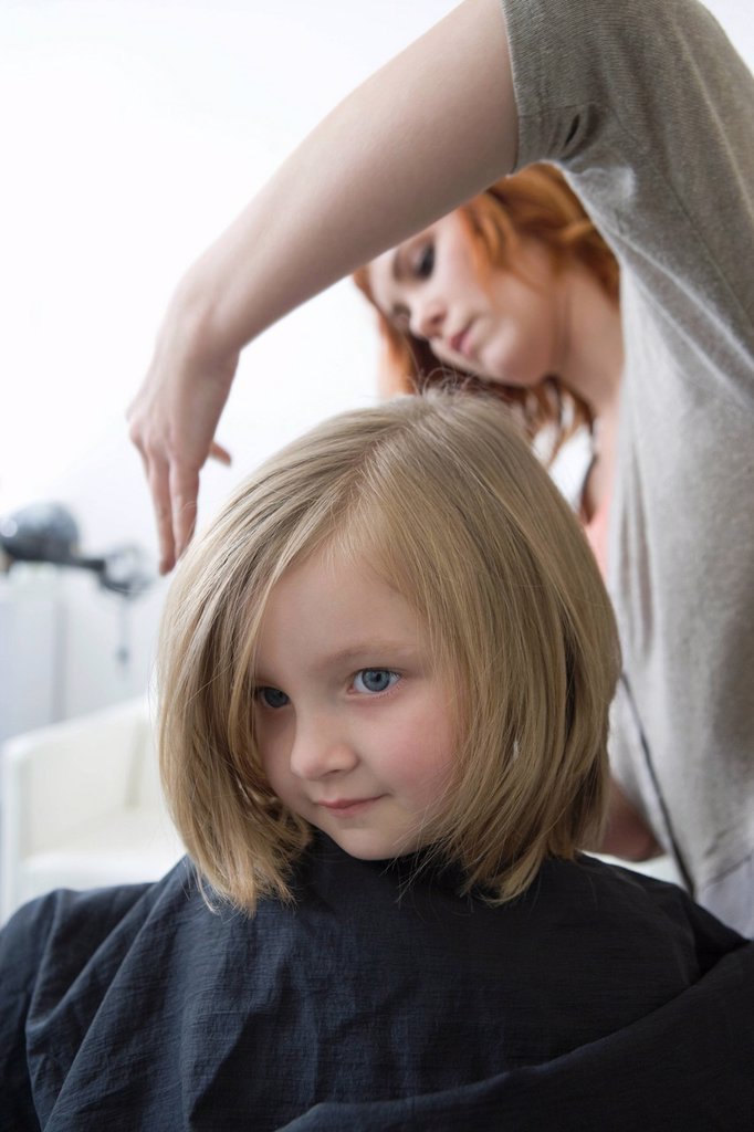 A young girl having her hair cut in the hairdressers : Stock Photo