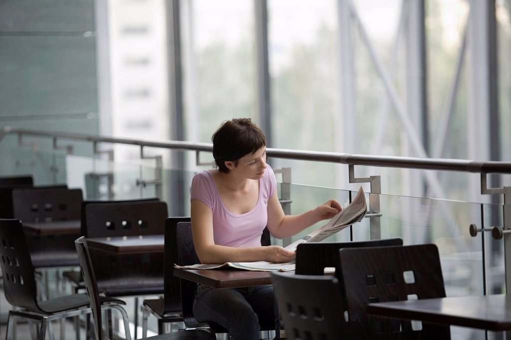 Young woman sits reading newspaper in food hall of shopping mall Voronezh : Stock Photo
