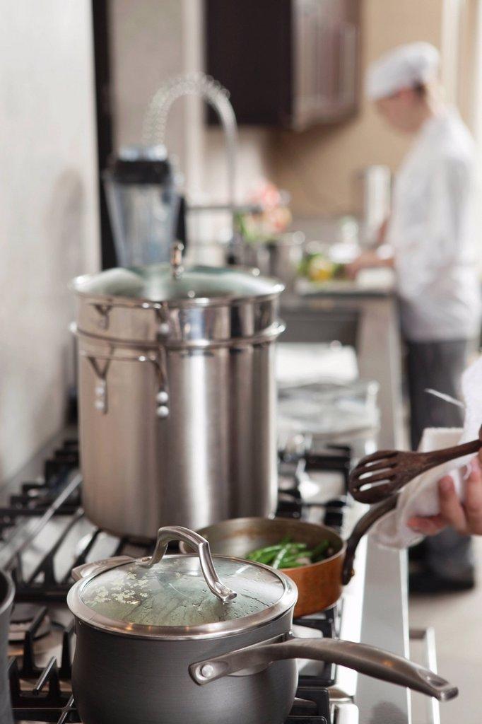 Stock Photo: 1654R-46736 Chef heating saucepan on hob