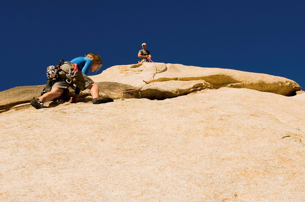 Stock Photo: 1654R-4680 Man assisting woman climbing cliff low angle view