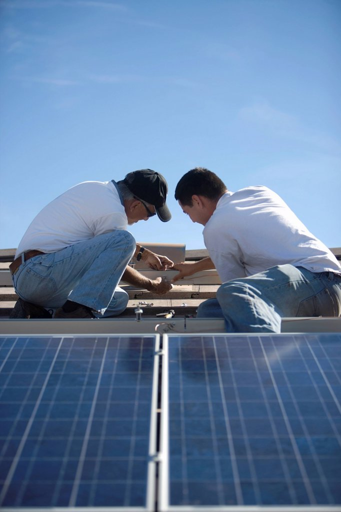 Two people on a rooftop working on solar panelling : Stock Photo