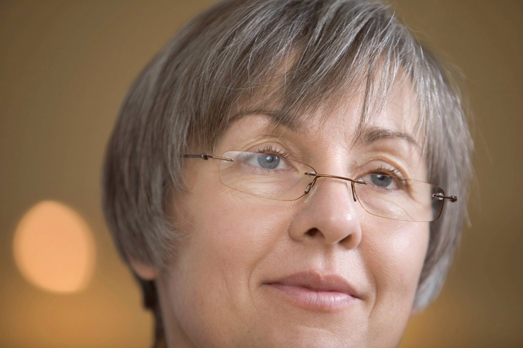 Mature woman with short grey hair in spectacles : Stock Photo
