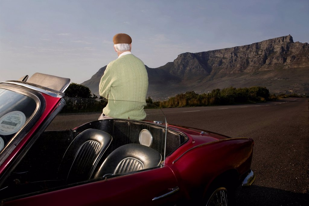 Senior man admires view leaning on vintage racing car on Signal Hill Cape Town South Africa : Stock Photo