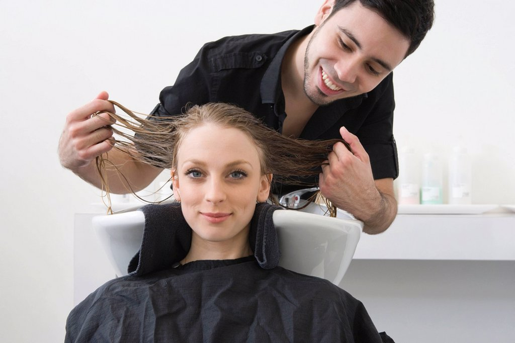 Man washing customers hair in the hairdressers : Stock Photo