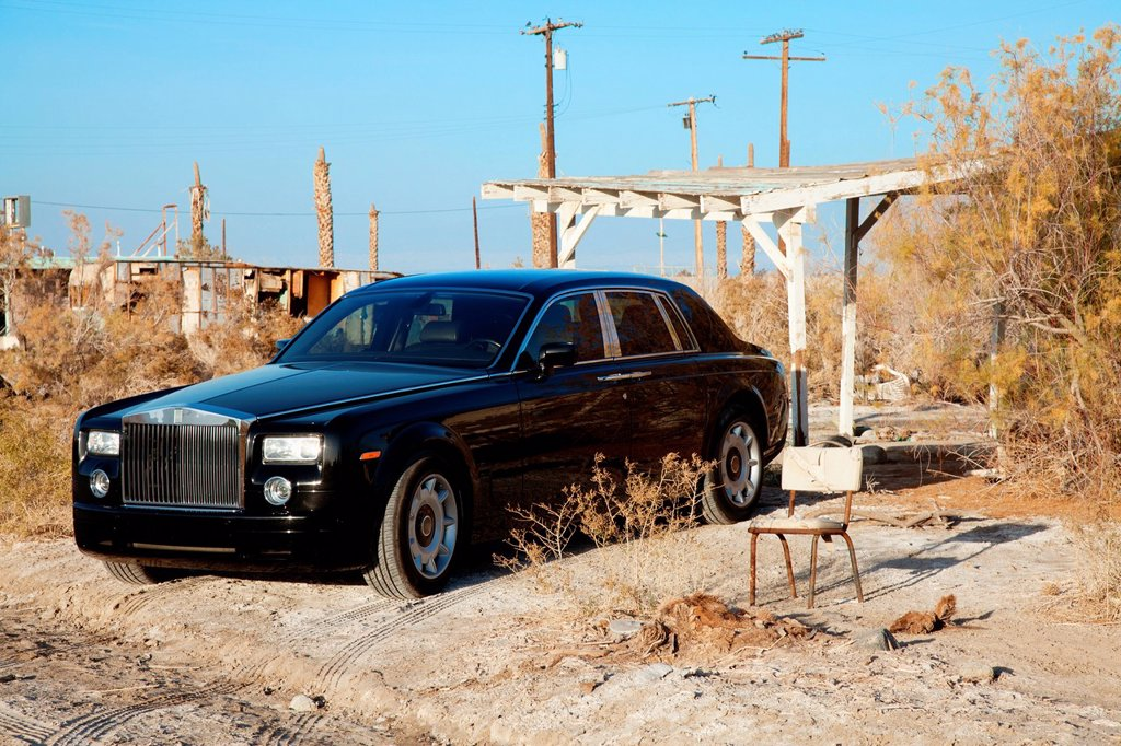 Stock Photo: 1654R-47531 Rolls Royce parked next to broken chair in abandoned village