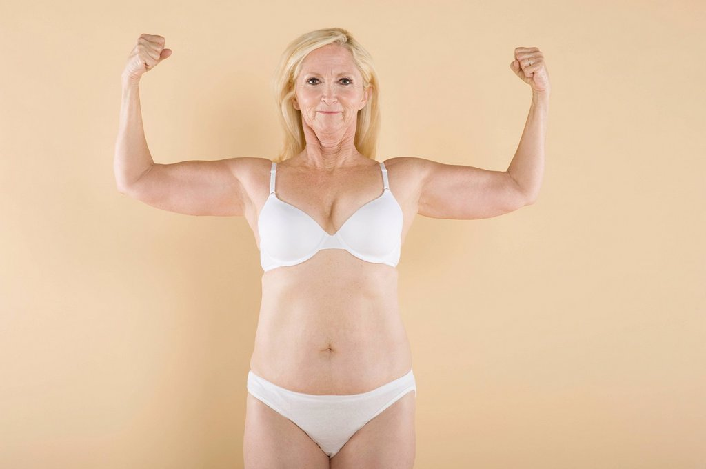 Mature woman flaunting her biceps and smiling : Stock Photo