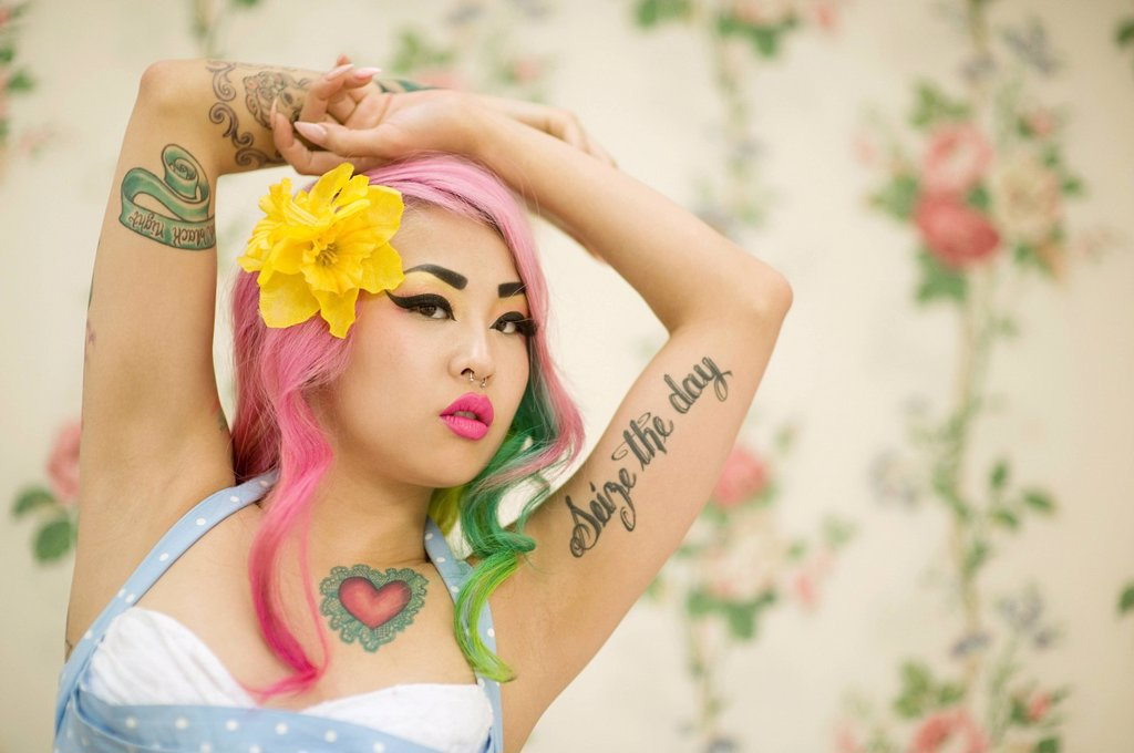 Stock Photo: 1654R-48010 Close_up of young woman with flower in head and arms raised