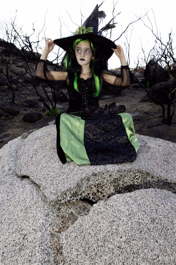 Little young girl costumed as witch sitting on rock looking away : Stock Photo