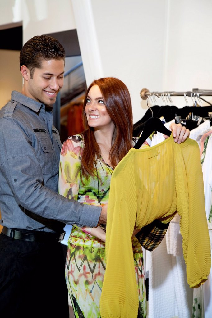 Happy young couple selecting a dress together in fashion boutique : Stock Photo