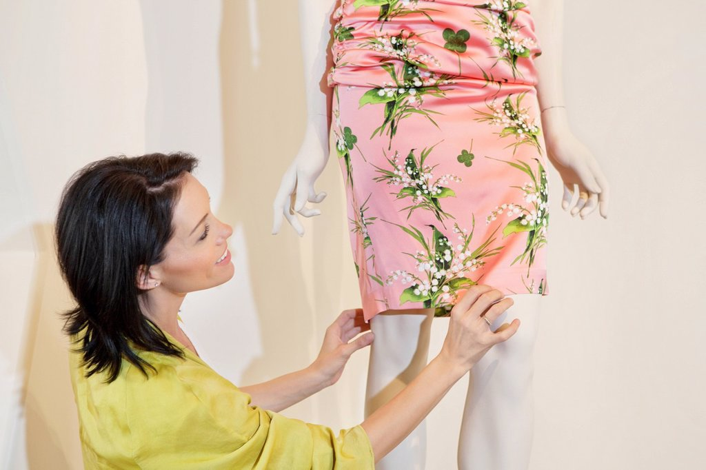 Stock Photo: 1654R-48613 Beautiful mid adult woman adjusting dress on mannequin in fashion store