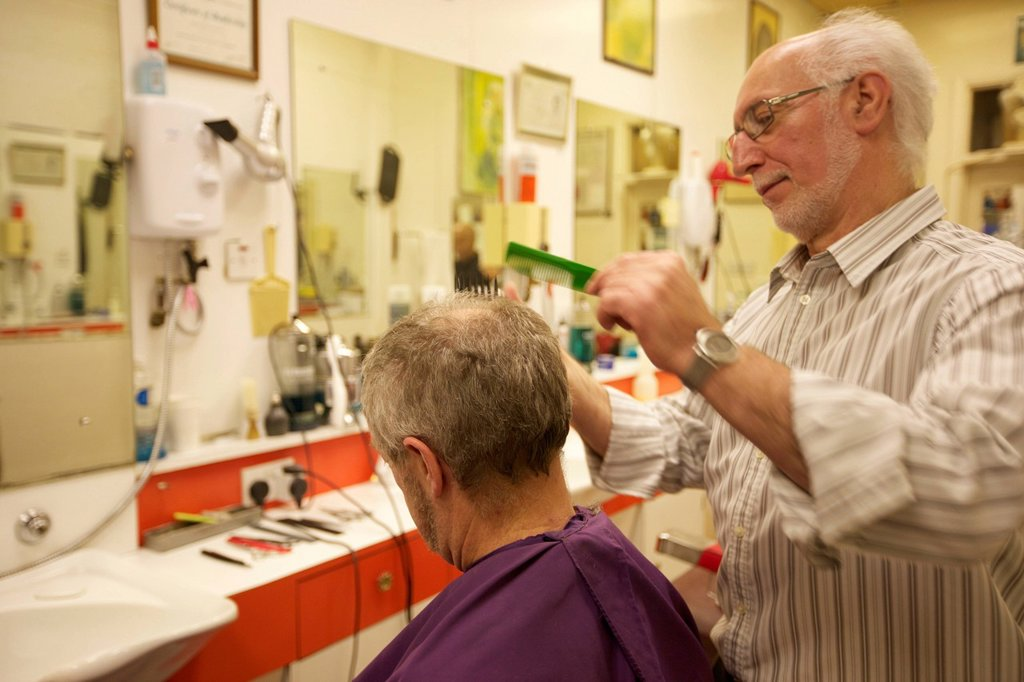 Stock Photo: 1654R-48675 Barber cutting senior man´s hair in barbershop