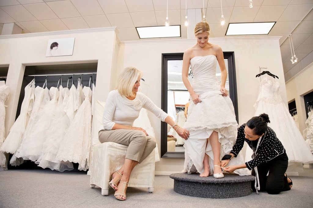 Stock Photo: 1654R-49850 Mother watching as mature employee helping bride with footwear in bridal boutique