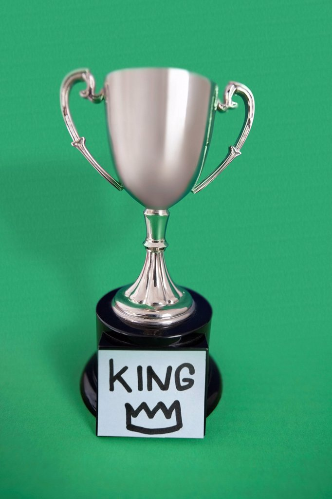 Stock Photo: 1654R-50022 Trophy with sticky note over colored background