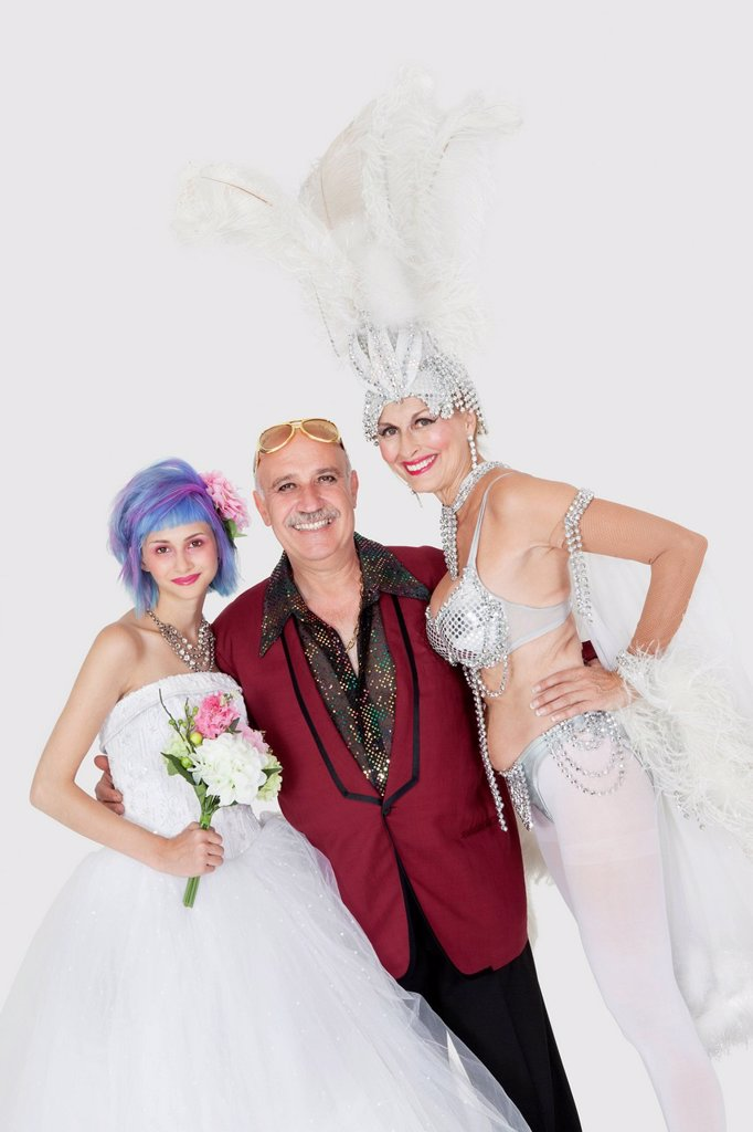 Portrait of man with senior showgirl and daughter in wedding dress over gray background : Stock Photo