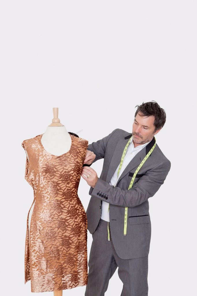 Mature male fashion designer adjusting cloth on tailor´s dummy over gray background : Stock Photo