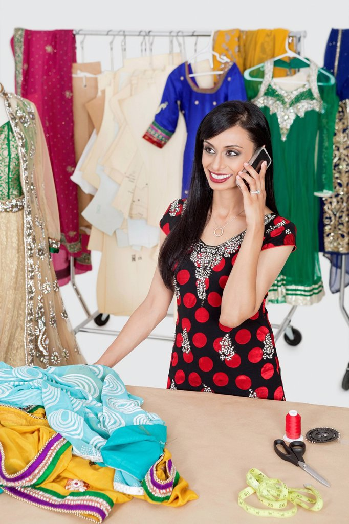 Pretty Indian female dressmaker answering phone call while standing at table : Stock Photo