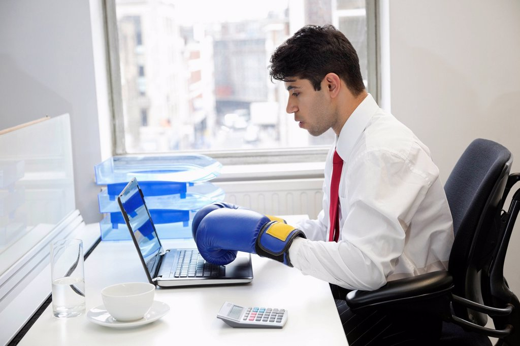Stock Photo: 1654R-51024 Young Indian businessman wearing boxing gloves while using laptop at office desk