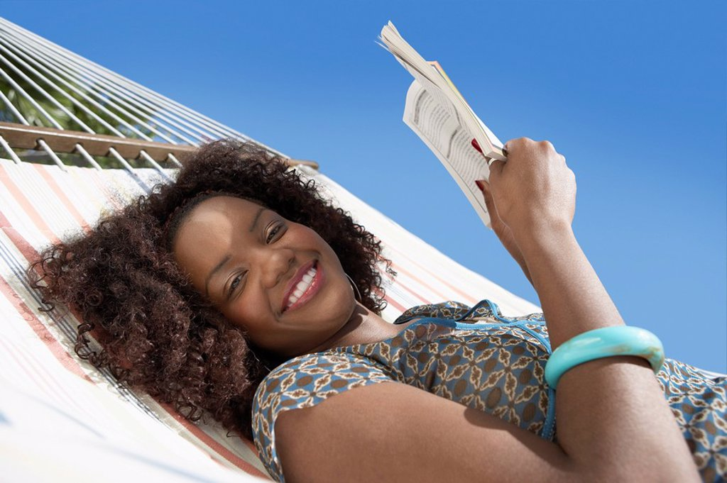 Woman reading in hammock half length : Stock Photo