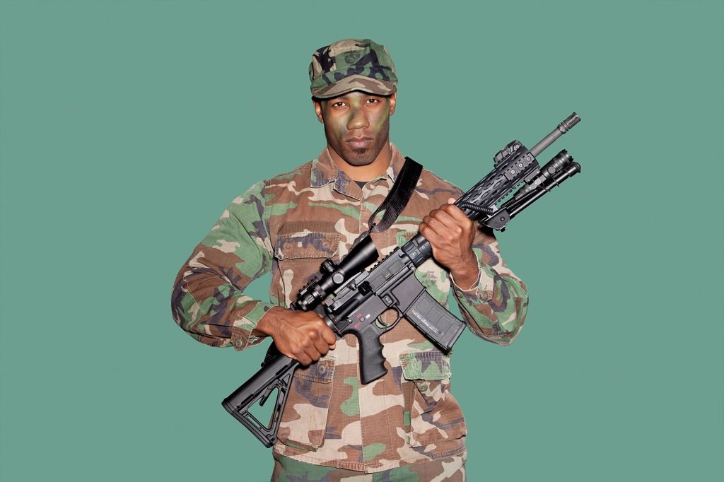 Stock Photo: 1654R-51170 Portrait of a young African American US Marine Corps soldier with M4 assault rifle over green background