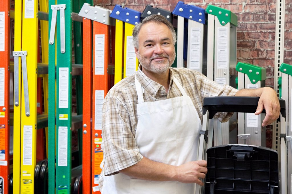 Portrait of happy mature store clerk standing by multicolored ladders in hardware shop : Stock Photo
