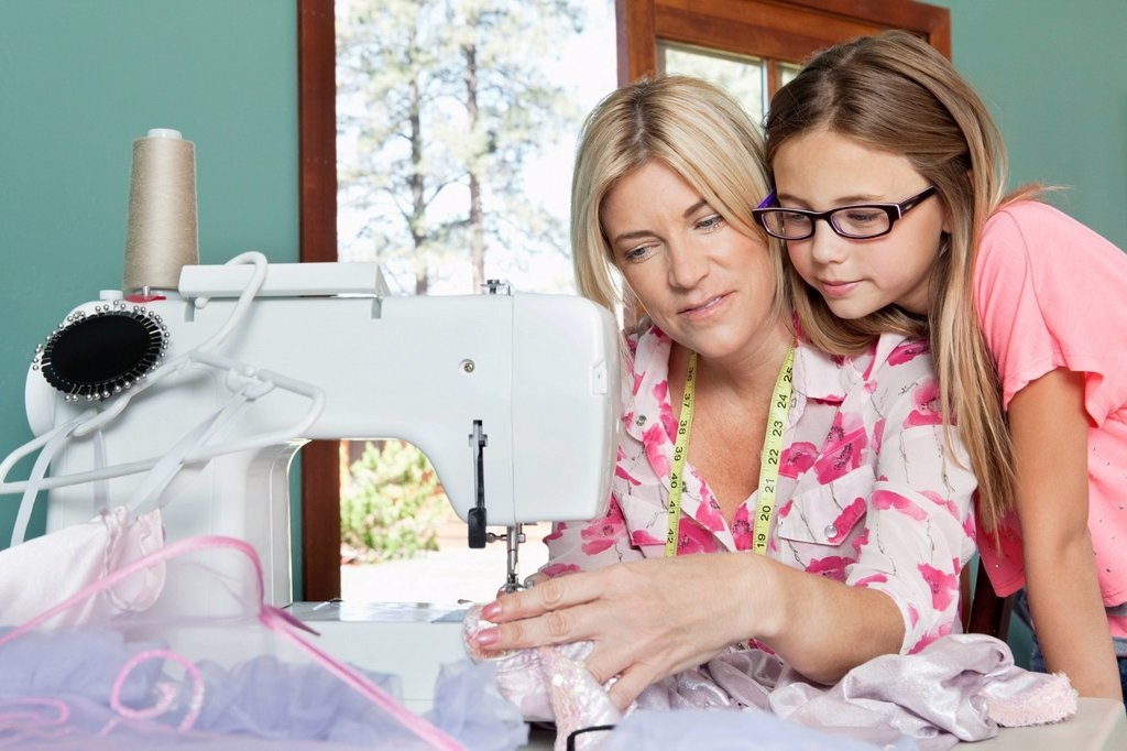 Stock Photo: 1654R-51492 Little girl looking at mother sewing cloth