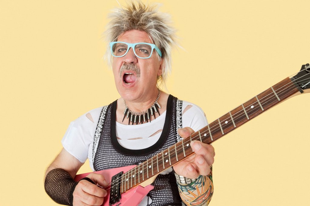Senior male punk musician playing guitar over yellow background : Stock Photo