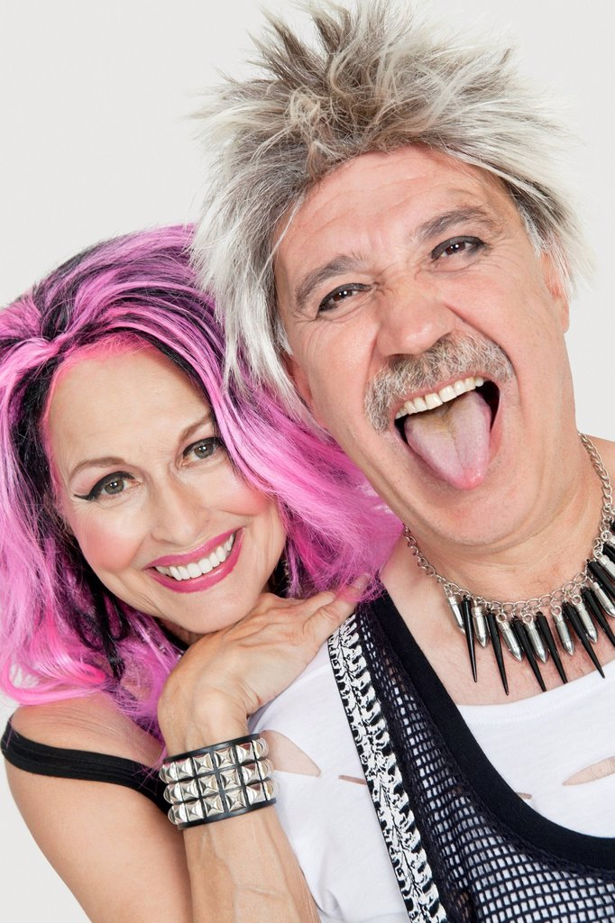 Stock Photo: 1654R-51621 Portrait of senior punk couple with man sticking out tongue over gray background