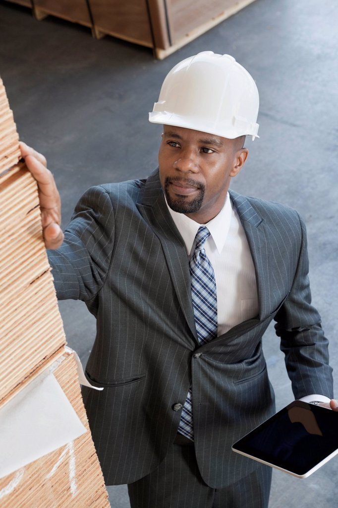 High angle view of African American male contractor inspecting wooden planks while holding tablet PC : Stock Photo