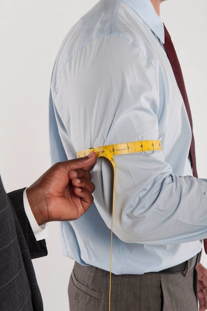 Tailor taking the measurement of a customer : Stock Photo