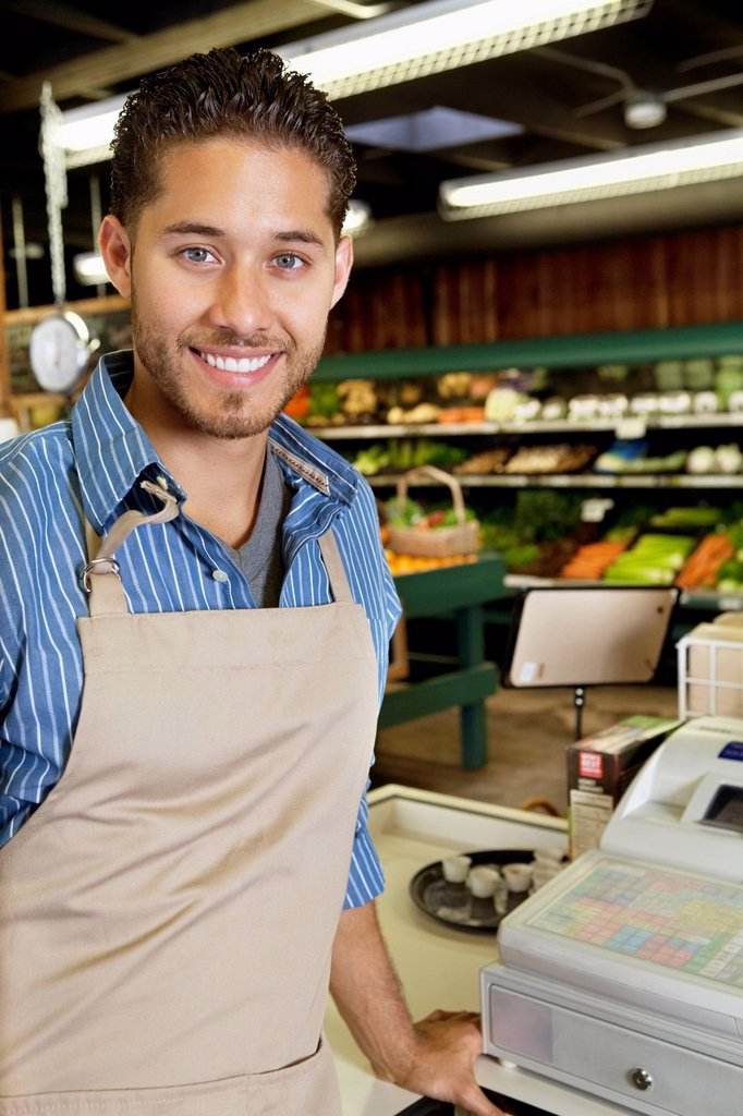 Portrait of handsome store employee standing near cash register in supermarket : Stock Photo
