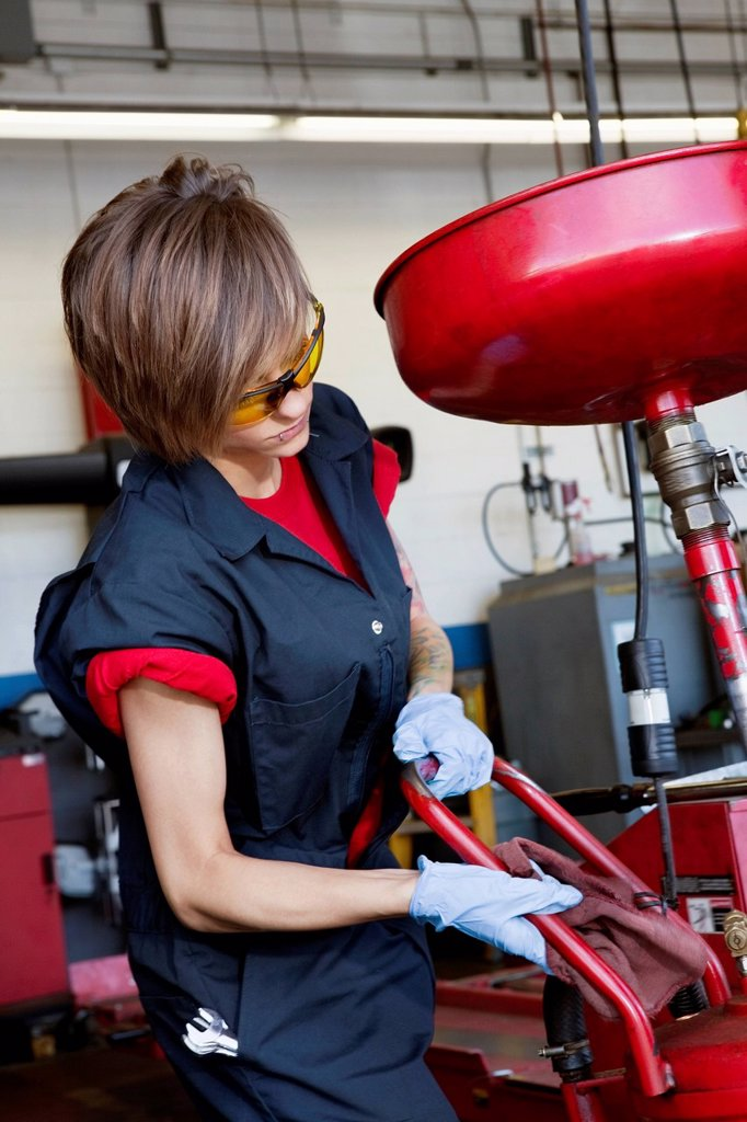 Young female mechanic working on welding equipment : Stock Photo