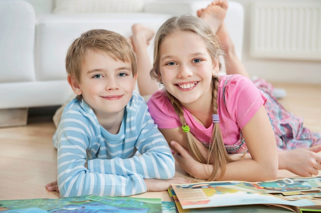 Stock Photo: 1654R-51863 Portrait of happy brother and sister with story books while lying on floor