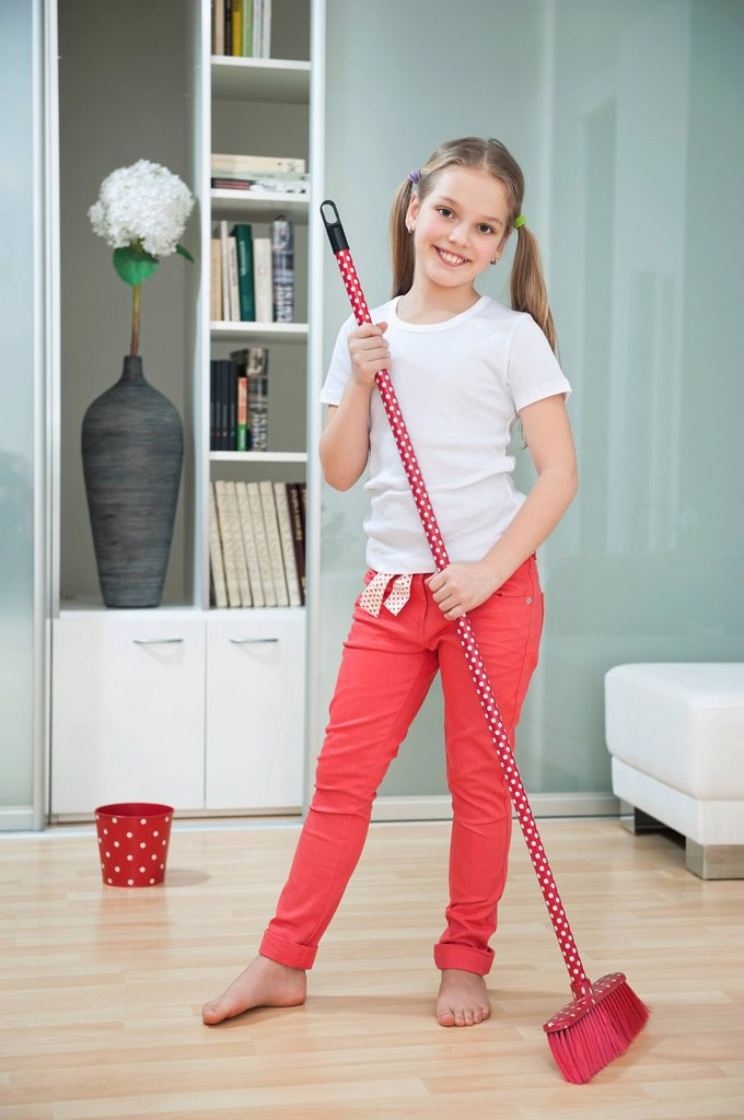 Portrait of a young girl sweeping floor with broom : Stock Photo