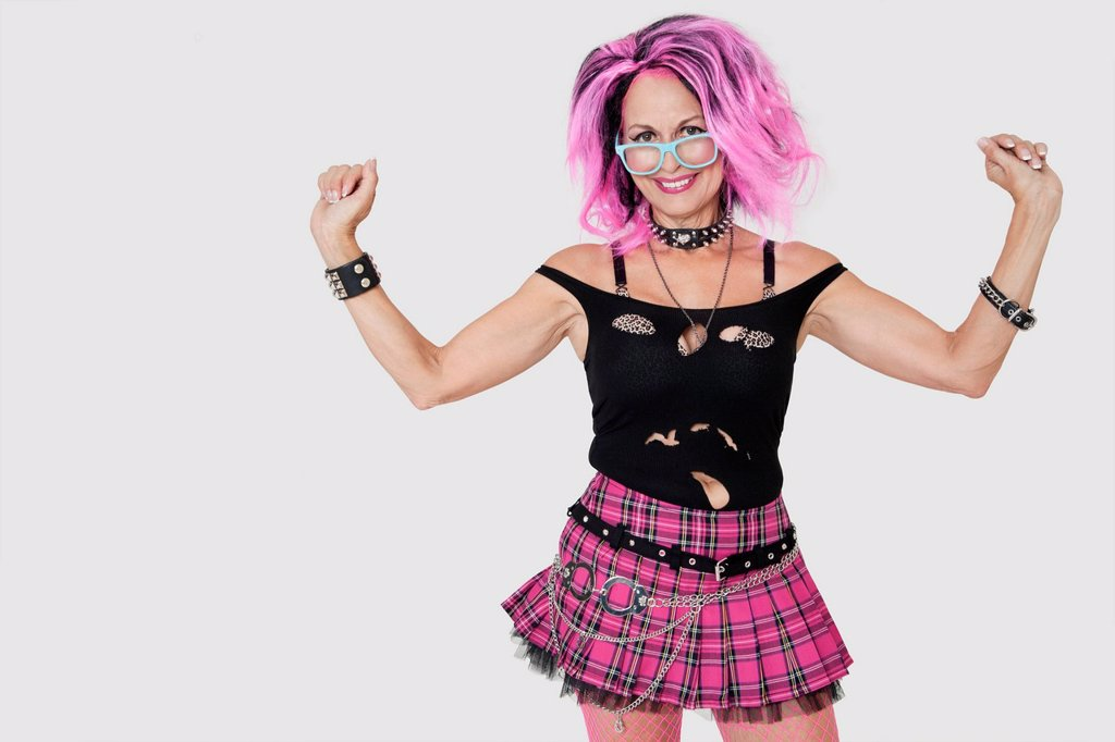 Portrait of senior female punk with raised arms over gray background : Stock Photo