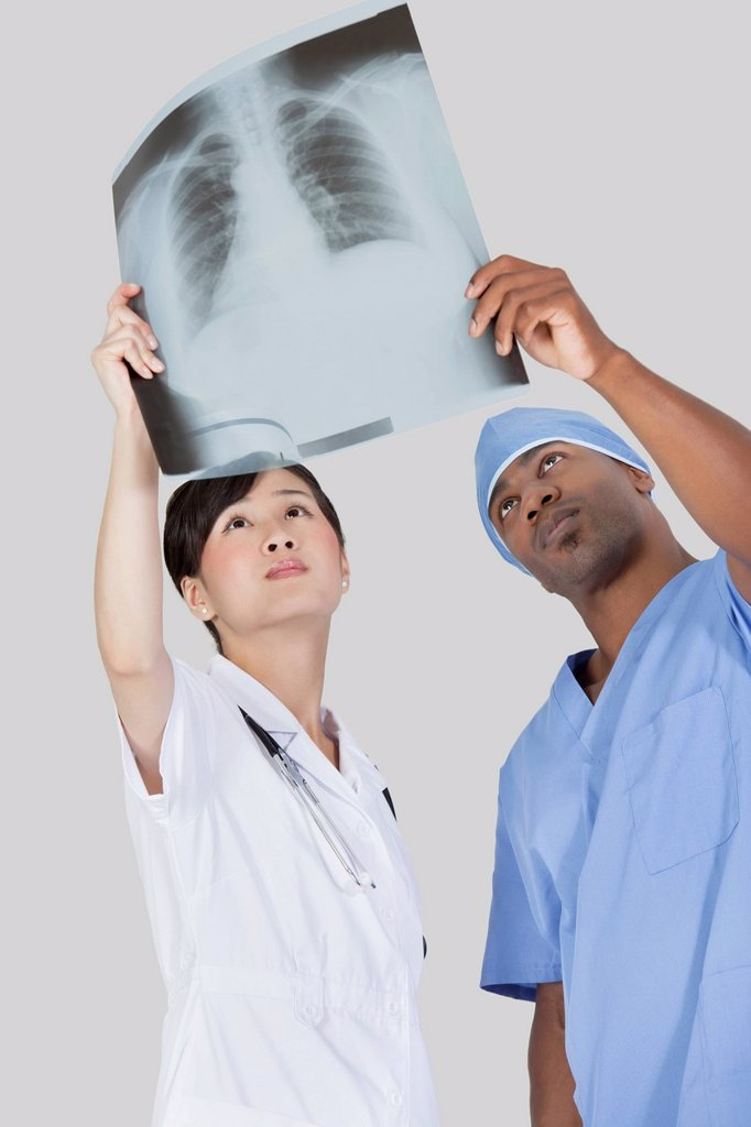 Male surgeon with nurse examining x_ray report over gray background : Stock Photo