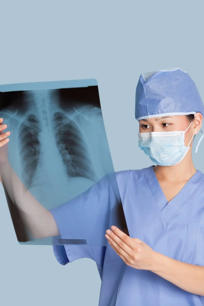 Female surgeon analyzing x_ray report over light blue background : Stock Photo