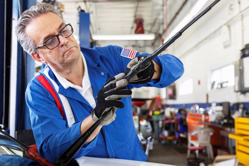 Stock Photo: 1654R-51989 Mechanic working on windshield wipers of car