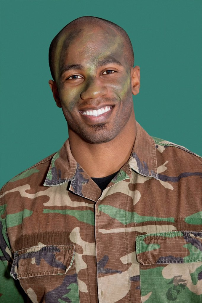 Stock Photo: 1654R-52064 Portrait of an African American male US Marine Corps soldier with camouflaged face over green background