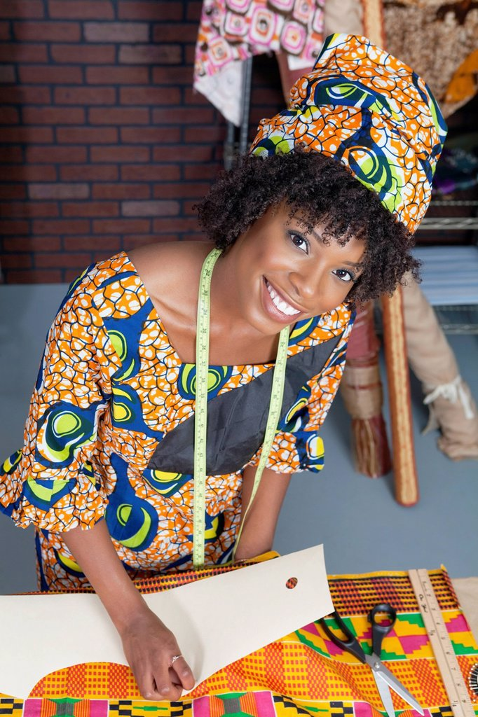 Stock Photo: 1654R-52163 Portrait of an African American female fashion designer working on fabric