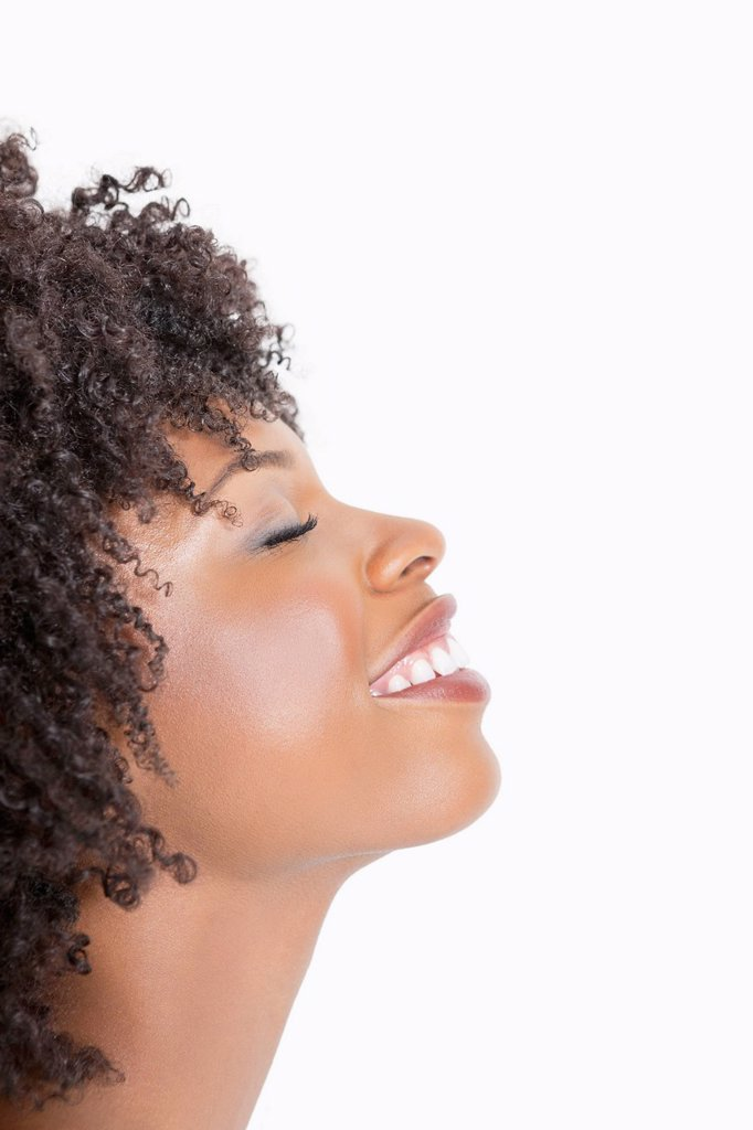 Stock Photo: 1654R-52207 Profile view of an African American woman smiling with eyes closed against gray background