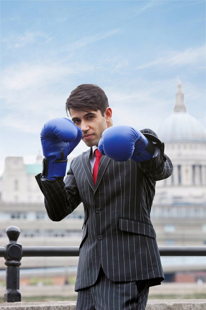 Stock Photo: 1654R-52214 Indian businessman wearing blue boxing gloves with St. Paul´s Cathedral in the background