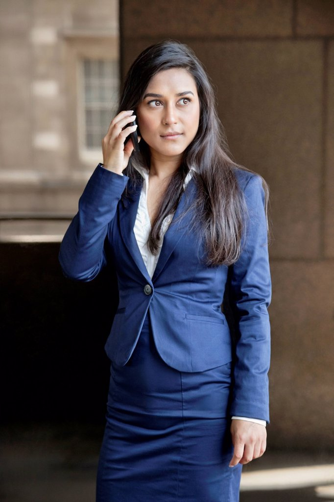 Stock Photo: 1654R-52216 Young Indian businesswoman looking away while using cell phone