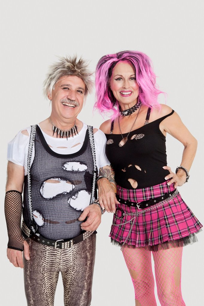 Stock Photo: 1654R-52233 Portrait of senior punk couple standing with arm in arm over gray background