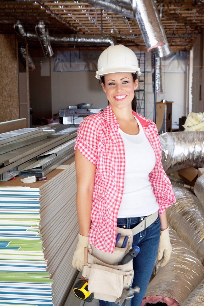 Portrait of a happy young woman architect wearing hardhat at construction site : Stock Photo