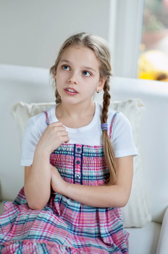 Stock Photo: 1654R-52254 Young girl thinking while sitting on sofa