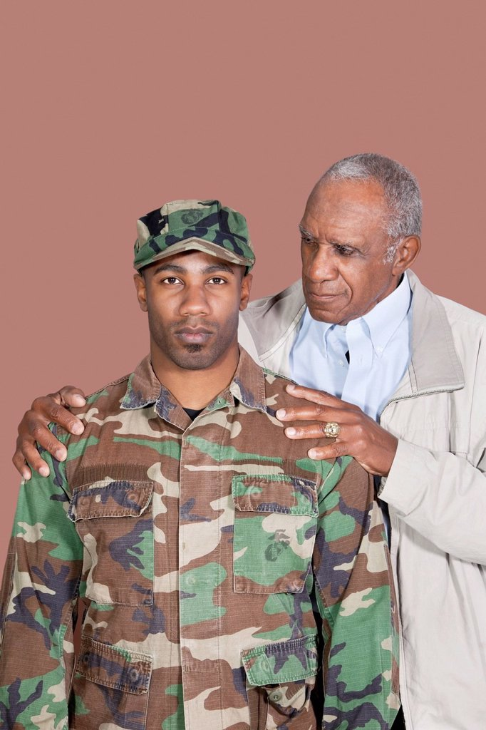 Portrait of African American male US Marine Corps soldier with father over brown background : Stock Photo