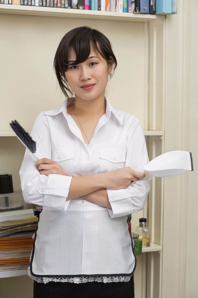 Portrait of young female housekeeper holding brush and dustpan : Stock Photo