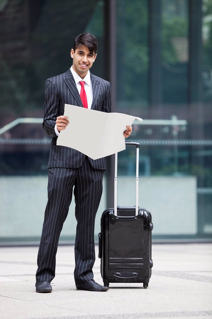 Stock Photo: 1654R-52444 Young Indian businessman with luggage bag reading paper