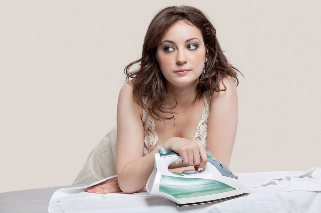 Stock Photo: 1654R-52449 Young woman looking away while ironing shirt over gray background